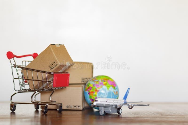 Κάρρο αγορών με τα χαρτοκιβώτια, τη σφαίρα αεροπλάνων και γης Σφαιρικές διοικητικές μέριμνες, ναυτιλία και παγκόσμια επιχειρησιακ στοκ εικόνα με δικαίωμα ελεύθερης χρήσης