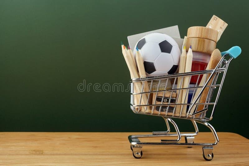 Κάρρο αγορών με τις σχολικές προμήθειες πέρα από το υπόβαθρο πινάκων κιμωλίας Πίσω στην έννοια σχολικής πώλησης στοκ φωτογραφία με δικαίωμα ελεύθερης χρήσης