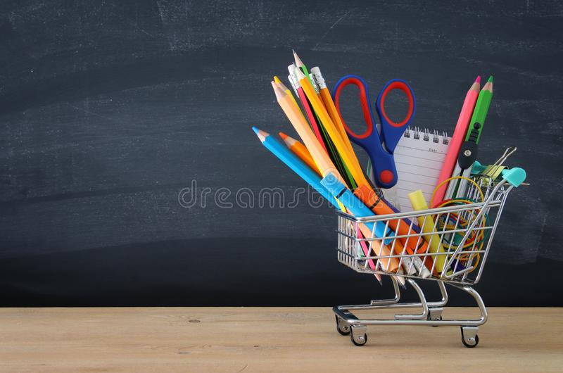 Κάρρο αγορών με το σχολικό ανεφοδιασμό μπροστά από τον πίνακα πίσω σχολείο έννοιας στοκ εικόνα με δικαίωμα ελεύθερης χρήσης