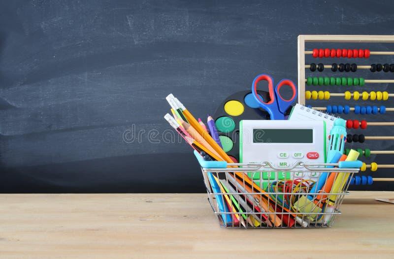 Κάρρο αγορών με το σχολικό ανεφοδιασμό μπροστά από τον πίνακα πίσω σχολείο έννοιας στοκ εικόνες με δικαίωμα ελεύθερης χρήσης