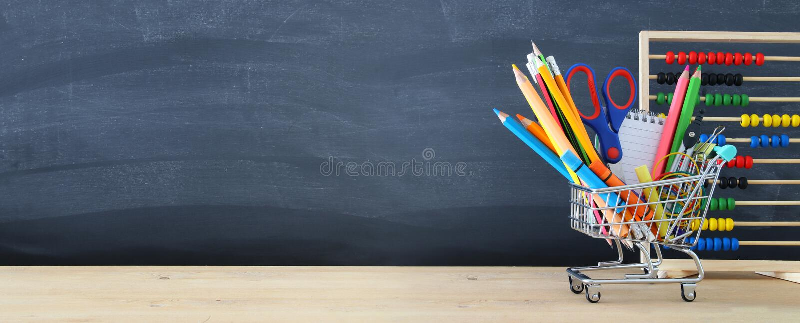 Κάρρο αγορών με το σχολικό ανεφοδιασμό μπροστά από τον πίνακα πίσω σχολείο έννοιας στοκ εικόνες
