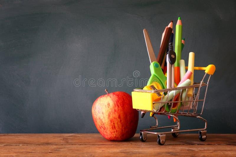Κάρρο αγορών με το σχολικούς ανεφοδιασμό και το μήλο στοκ φωτογραφία με δικαίωμα ελεύθερης χρήσης