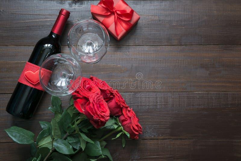 Κάρτα βαλεντίνων με τα ρομαντικά κόκκινα τριαντάφυλλα, το μπουκάλι κρασιού, την καρδιά και το κόκκινο κιβώτιο δώρων στον ξύλινο π στοκ εικόνες με δικαίωμα ελεύθερης χρήσης