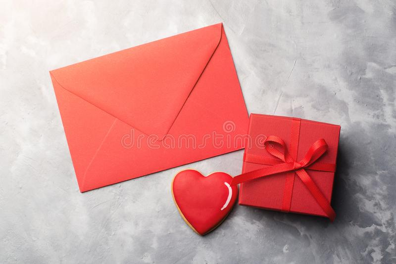 Κάρτα βαλεντίνων με τον κόκκινο φάκελο, το κιβώτιο δώρων και το μελόψωμο καρδιών στο γκρίζο κατασκευασμένο υπόβαθρο στοκ φωτογραφία