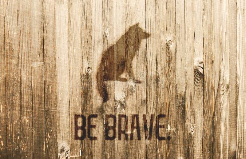Κάρτα κινήτρου Λύκος συνεδρίασης που καίγεται στις ξύλινες σανίδες Το κείμενο είναι γενναίο στοκ φωτογραφία