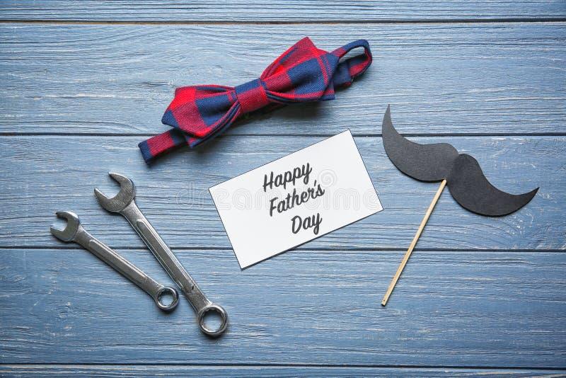 Κάρτα με ευτυχής πατέρας \ «s κειμένων \ «ημέρα \», δεσμός τόξων και εργαλεία στο ξύλινο υπόβαθρο στοκ εικόνα
