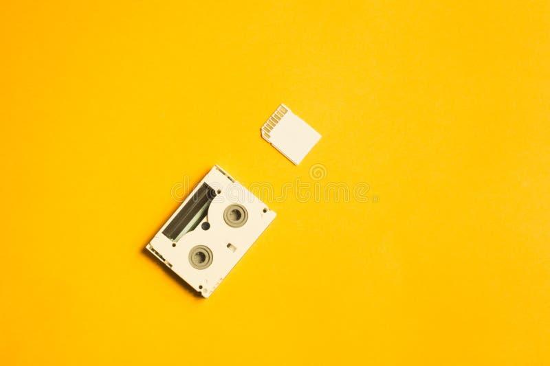 Κάρτα μνήμης και ψηφιακή τηλεοπτική κασέτα στο κίτρινο υπόβαθρο διάστημα αντιγράφων στοκ εικόνες