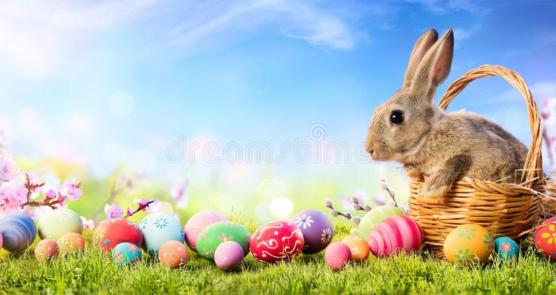 Κάρτα Πάσχας - λίγο λαγουδάκι στο καλάθι με τα διακοσμημένα αυγά στοκ εικόνες