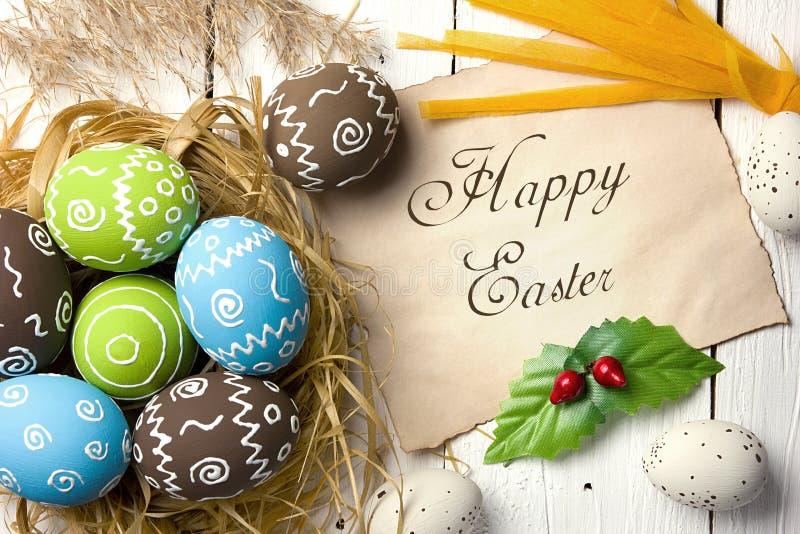 κάρτα Πάσχα Χρωματισμένα αυγά Πάσχας με το κομμάτι χαρτί για τα συγχαρητήρια σε ένα φυσικό ξύλινο υπόβαθρο στοκ φωτογραφίες με δικαίωμα ελεύθερης χρήσης