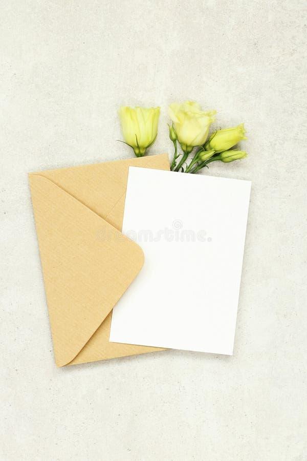 Κάρτα πρόσκλησης προτύπων στο γκρίζο υπόβαθρο με το φάκελο και τα άσπρα τριαντάφυλλα στοκ φωτογραφία