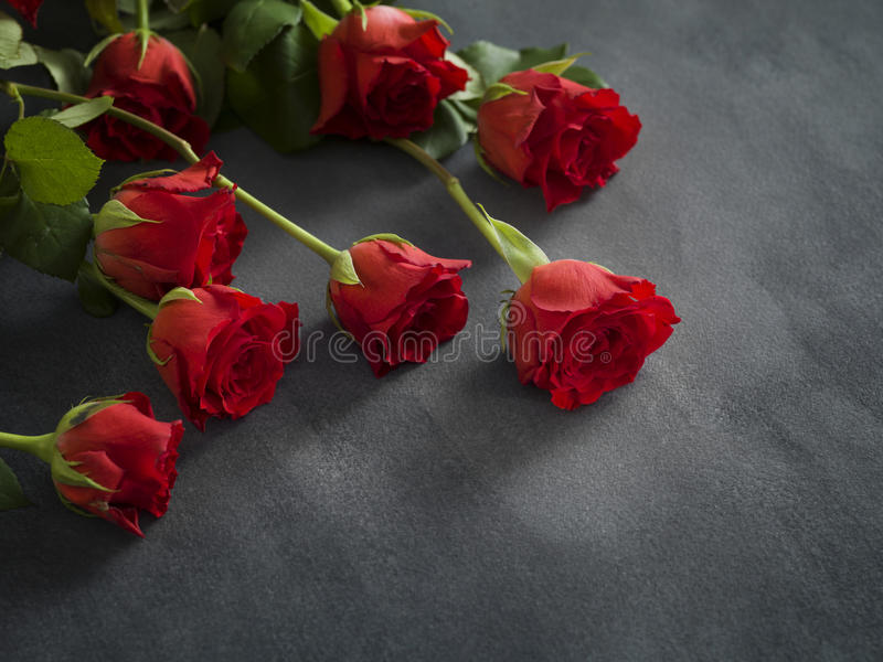 Κάρτα συλληπητήριων με τα κόκκινα τριαντάφυλλα στο γκρίζο υπόβαθρο στοκ φωτογραφίες με δικαίωμα ελεύθερης χρήσης