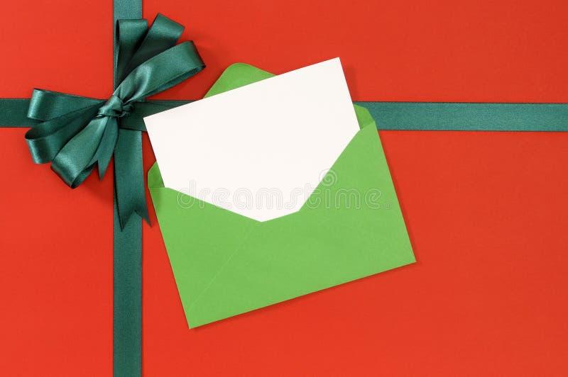 Κάρτα Χριστουγέννων, κόκκινο υπόβαθρο εγγράφου περικαλυμμάτων δώρων, πράσινο τόξο κορδελλών δώρων, φάκελος, διάστημα αντιγράφων στοκ φωτογραφίες