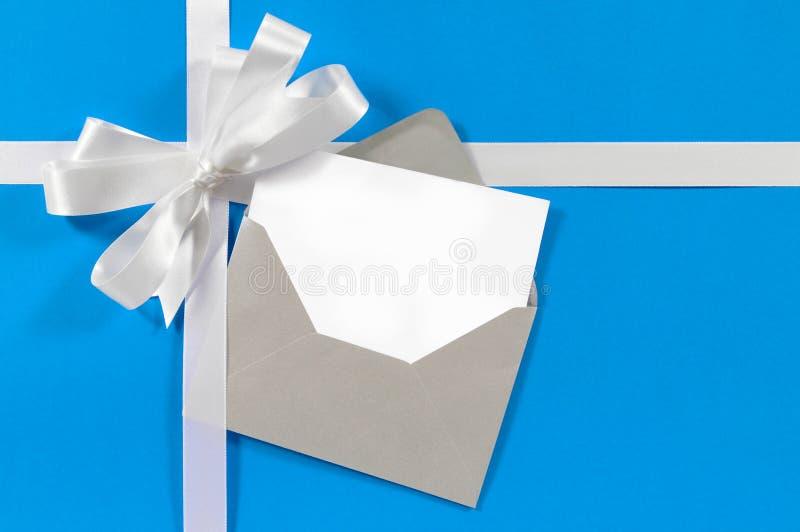 Κάρτα Χριστουγέννων με το τόξο κορδελλών δώρων στο άσπρο σατέν στο μπλε υπόβαθρο εγγράφου στοκ φωτογραφίες