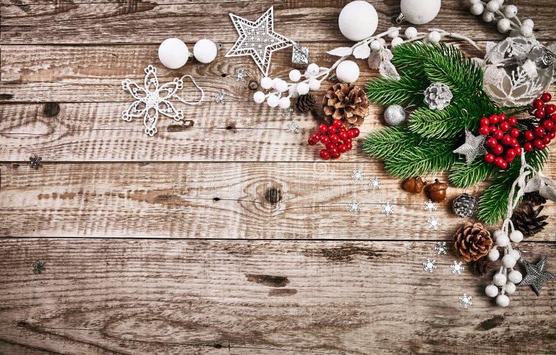 Κάρτα Χριστουγέννων με firtree τις σφαίρες pinecone και γυαλιού στον παλαιό ξύλινο πίνακα στο αγροτικό ύφος copyspace στοκ φωτογραφίες