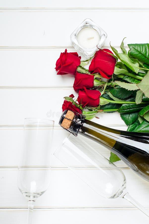 Κάρτες ημέρας βαλεντίνων Ανθοδέσμη των κόκκινων τριαντάφυλλων στο λευκό ξύλινο πίνακα Τοπ όψη στοκ εικόνες