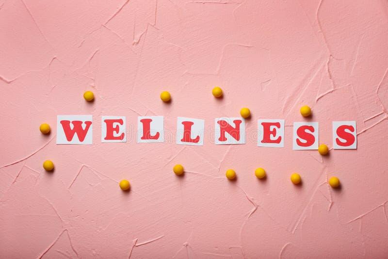 Κάρτες με τη λέξη WELLNESS και χάπια στο υπόβαθρο χρώματος E στοκ φωτογραφία