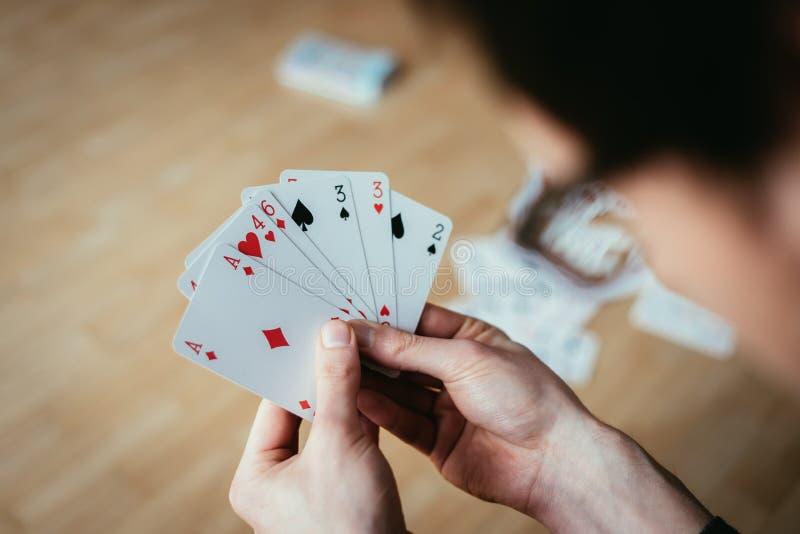 Κάρτες παιχνιδιού: Κάρτες πόκερ στο χέρι ενός νεαρού άνδρα στοκ εικόνα με δικαίωμα ελεύθερης χρήσης