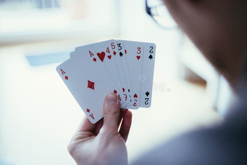 Κάρτες παιχνιδιού: Κάρτες πόκερ στο χέρι ενός νεαρού άνδρα στοκ εικόνες με δικαίωμα ελεύθερης χρήσης