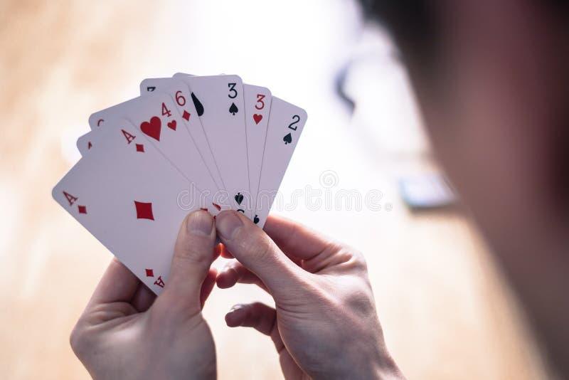 Κάρτες παιχνιδιού: Κάρτες πόκερ στο χέρι ενός νεαρού άνδρα στοκ εικόνα