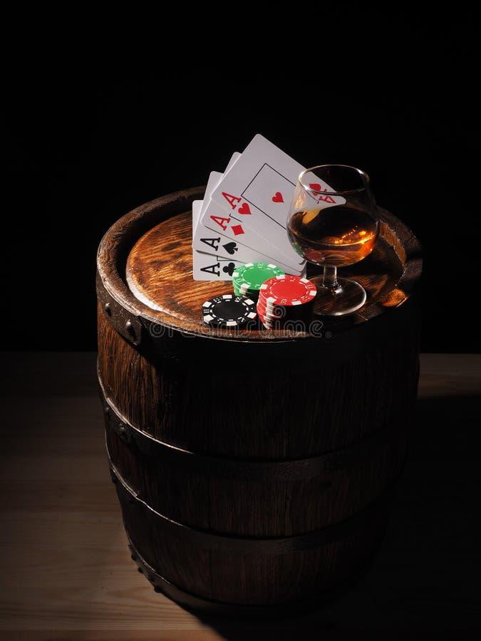 Κάρτες παιχνιδιού και ποτήρι κρασιού του κονιάκ στο βαρέλι στοκ φωτογραφίες