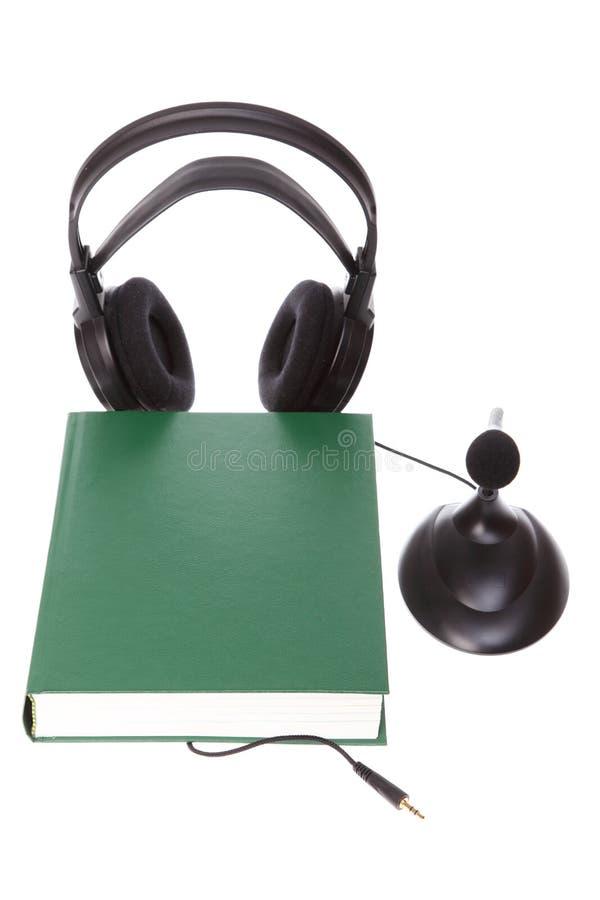Κάσκα με το μικρόφωνο, hardcover βιβλίο που απομονώνεται στοκ εικόνα