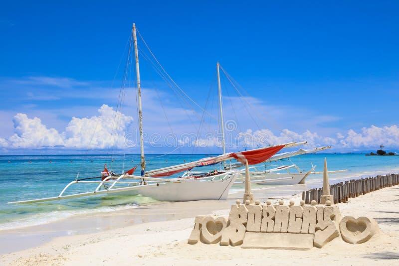 Κάστρο άμμου και μια βάρκα πανιών στην άσπρη παραλία, νησί Boracay, Φιλιππίνες στοκ εικόνα με δικαίωμα ελεύθερης χρήσης
