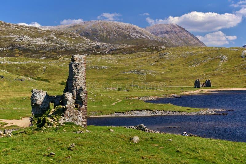 Κάστρο στο lakeshore με τη σειρά βουνών στην απόσταση στοκ εικόνες