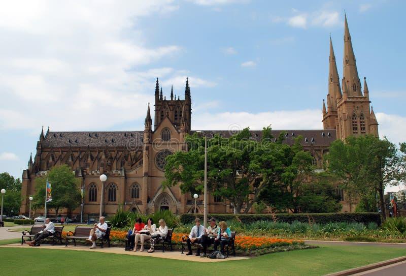 Κάτοικοι και τουρίστες του Σίδνεϊ που απολαμβάνουν τη μεσημβρία στους πάγκους του πάρκου Hyde μπροστά από τον καθεδρικό ναό του S στοκ φωτογραφία με δικαίωμα ελεύθερης χρήσης