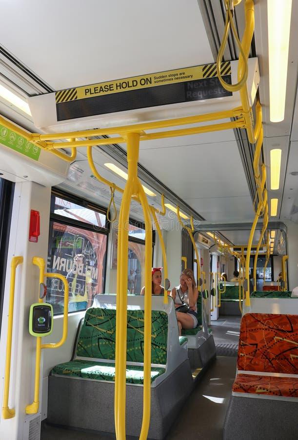 Κάτοχοι διαρκούς εισιτήριου και εσωτερικό ενός τραμ δημόσιων συγκοινωνιών που παρουσιάζει παρακαλώ λαβή στο σημάδι προσοχής, το κ στοκ φωτογραφία με δικαίωμα ελεύθερης χρήσης