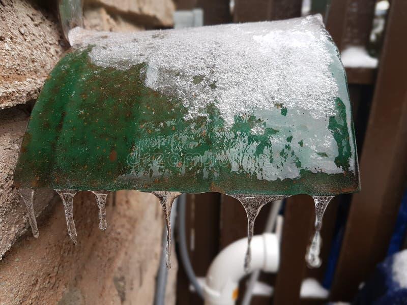 Κάτοχος μανικών νερού που καλύπτεται από τον πάγο από τη βροχή παγώματος στοκ φωτογραφίες