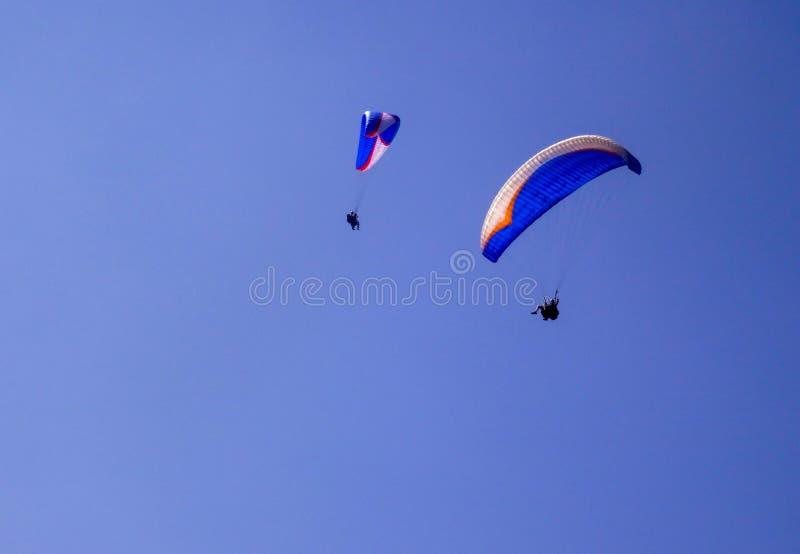 Κάτω από δύο κρεμάστε τα ανεμοπλάνα σε έναν ανοικτό μπλε ουρανό στοκ εικόνες