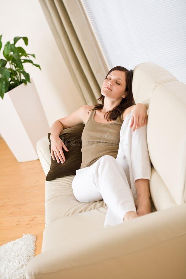 κάτω από ευτυχές να βρεθεί χαλαρώστε τις νεολαίες γυναικών καναπέδων στοκ εικόνες
