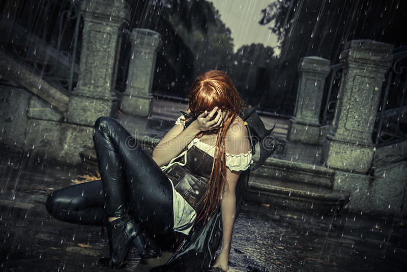 Κάτω από τη θύελλα, όμορφη γυναίκα βαμπίρ στην πύλη παλατιών, βροχή στοκ φωτογραφία