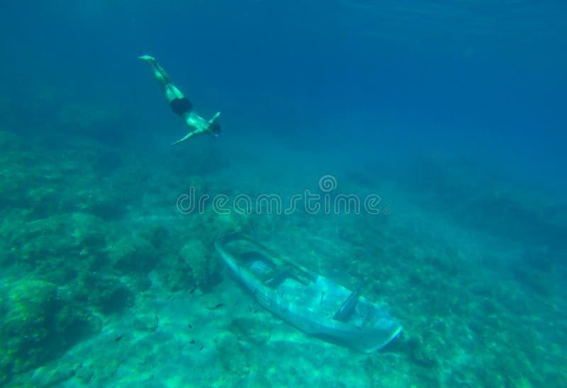 Κάτω από το νερό το νέο αγόρι κολυμπά στη βυθισμένη βάρκα στοκ φωτογραφία με δικαίωμα ελεύθερης χρήσης