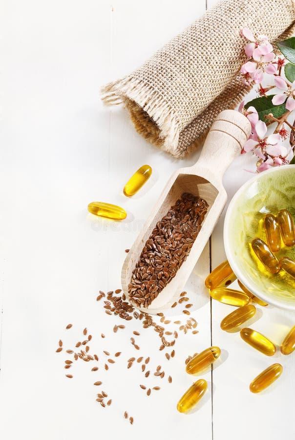 Κάψες πετρελαίου λιναρόσπορου και flaxseed πέρα από το άσπρο υπόβαθρο στοκ εικόνα