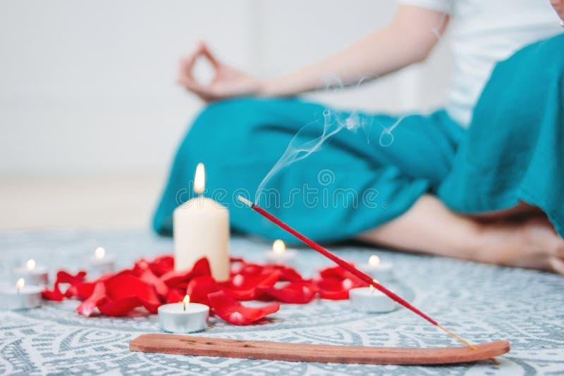 Κάψιμο του κόκκινου ραβδιού θυμιάματος στο υπόβαθρο κεριών και τη γιόγκα άσκησης γυναικών στοκ φωτογραφίες