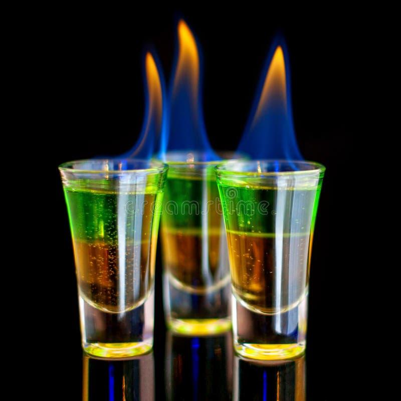 Κάψιμο του πράσινου κοκτέιλ στο πυροβοληθε'ν γυαλί στο μαύρο υπόβαθρο στοκ φωτογραφία