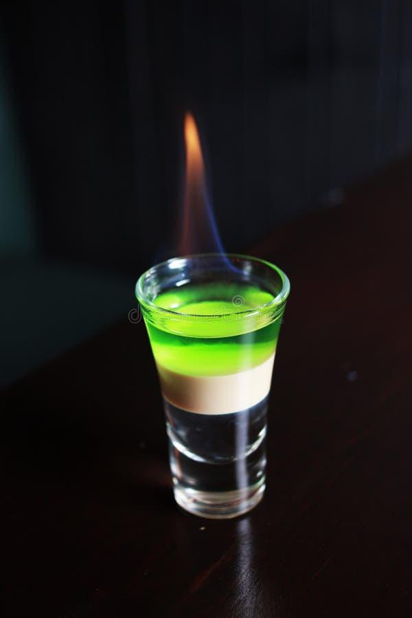 Κάψιμο του ριγωτού πολυστρωματικού ποτού οινοπνεύματος στο πυροβοληθε'ν γυαλί σε ένα tabl στοκ εικόνες με δικαίωμα ελεύθερης χρήσης
