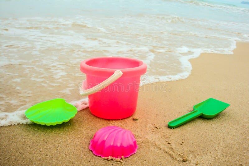 Κάδος παιδιών ` s και χρωματισμένες φόρμες στην παραλία στην άμμο στοκ εικόνες