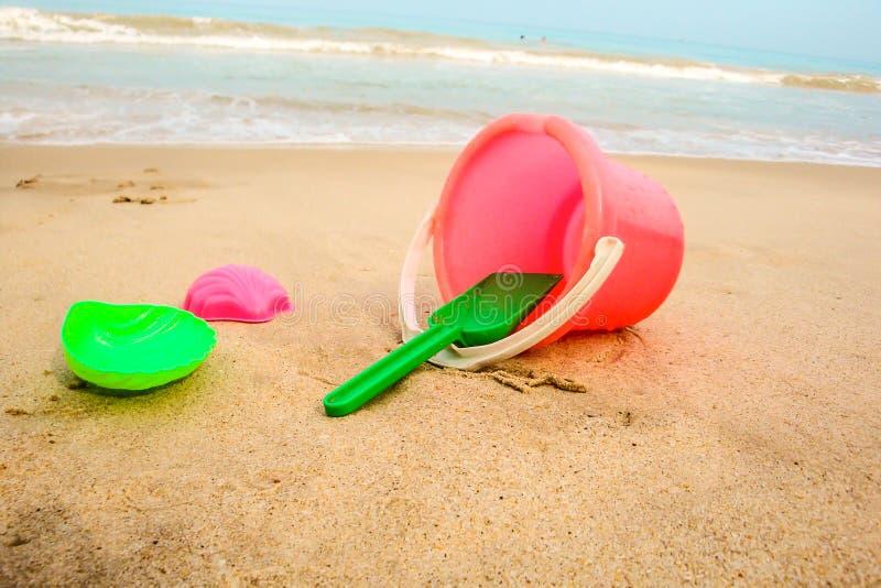 Κάδος παιδιών ` s και χρωματισμένες φόρμες στην παραλία στην άμμο στοκ φωτογραφία με δικαίωμα ελεύθερης χρήσης