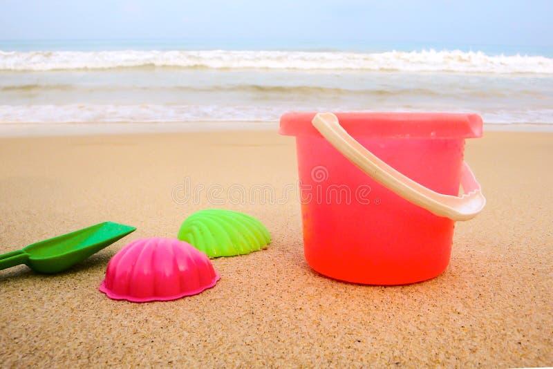 Κάδος παιδιών ` s και χρωματισμένες φόρμες στην παραλία στην άμμο στοκ φωτογραφίες