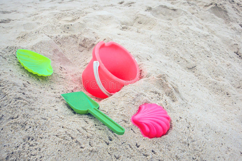 Κάδος παιδιών ` s και χρωματισμένες φόρμες στην παραλία στην άμμο στοκ φωτογραφίες με δικαίωμα ελεύθερης χρήσης