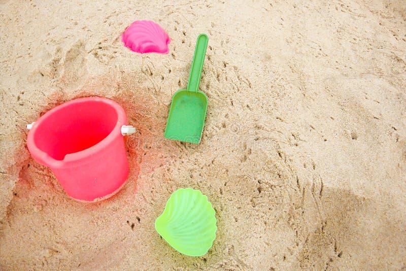 Κάδος παιδιών ` s και χρωματισμένες φόρμες στην παραλία στην άμμο στοκ φωτογραφία