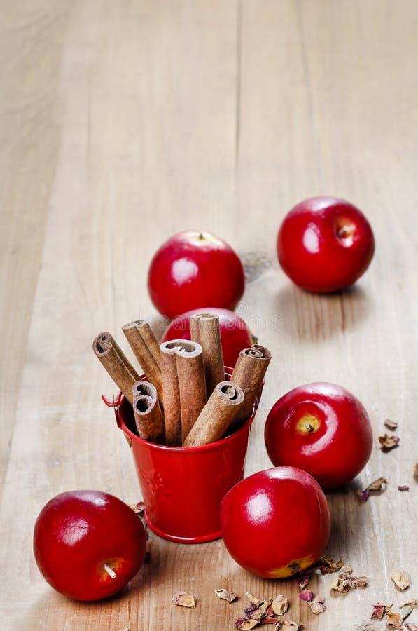 Κάδος των ραβδιών κανέλας στον ξύλινο πίνακα. Κόκκινα μήλα γύρω στοκ εικόνες με δικαίωμα ελεύθερης χρήσης