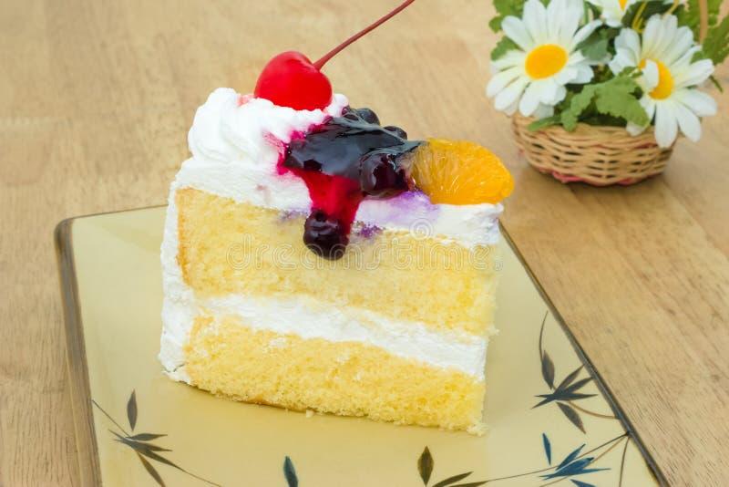 Κάλυμμα κέικ βανίλιας με το κεράσι, πορτοκάλι, βακκίνιο στοκ εικόνες
