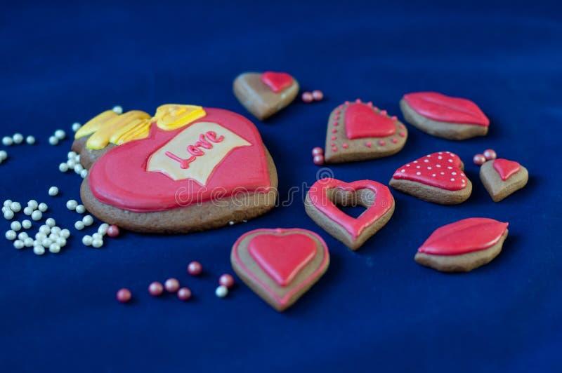 Κέικ βαλεντίνων ` s του ST Η καρδιά και διαμορφωμένα τα χείλια κέικ μελιού βάζουν στο μπλε υπόβαθρο στοκ φωτογραφίες