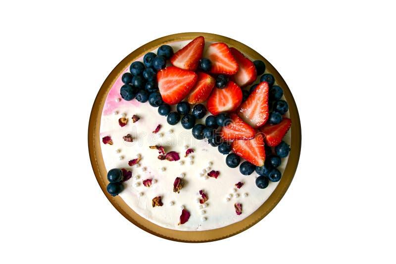 Κέικ γενεθλίων που διακοσμείται με τα παγώνοντας, φρέσκες βακκίνια άσπρων τυριών κρέμας και φέτες των φραουλών στοκ εικόνες