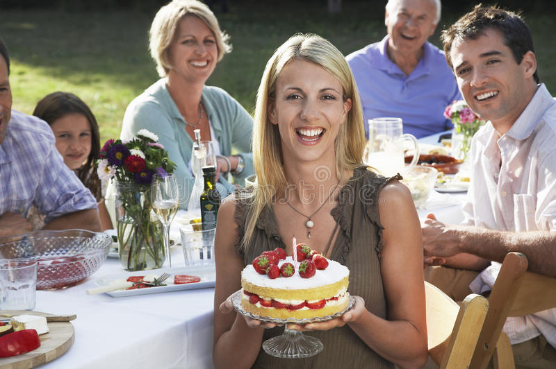 Κέικ γενεθλίων εκμετάλλευσης γυναικών με την οικογένεια στον κήπο στοκ εικόνες