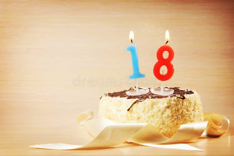Κέικ γενεθλίων με το κάψιμο του κεριού ως αριθμό δεκαοχτώ στοκ φωτογραφίες