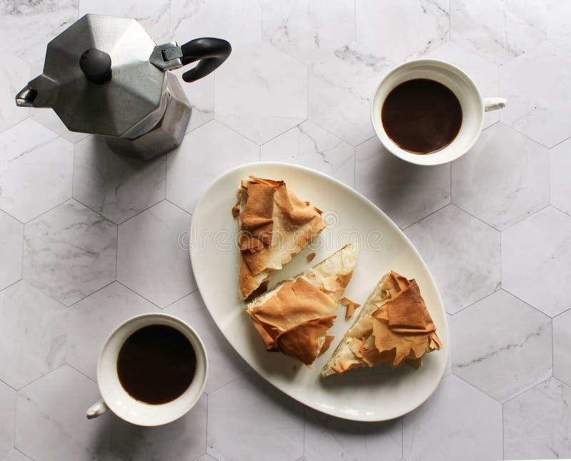Κέικ ζύμης Filo προγευμάτων σε ένα άσπρο πιάτο geyser κατασκευαστής καφέ, φλυτζάνια καφέ σε έναν μαρμάρινο πίνακα στοκ φωτογραφία με δικαίωμα ελεύθερης χρήσης
